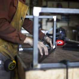 Custom furniture craftsman assembles stool support structure.
