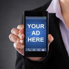 """Woman holding a mobile phone with showing the message of """"Your ad here""""."""